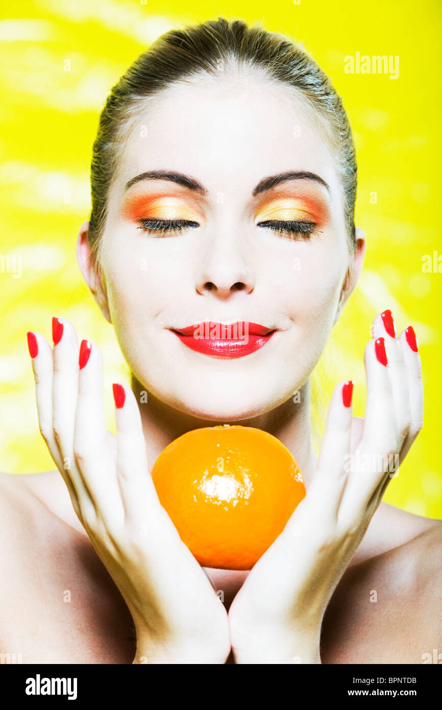 beautiful caucasian woman portrait smelling a citrus fruit pleasure smile studio on yellow background Stock Photo
