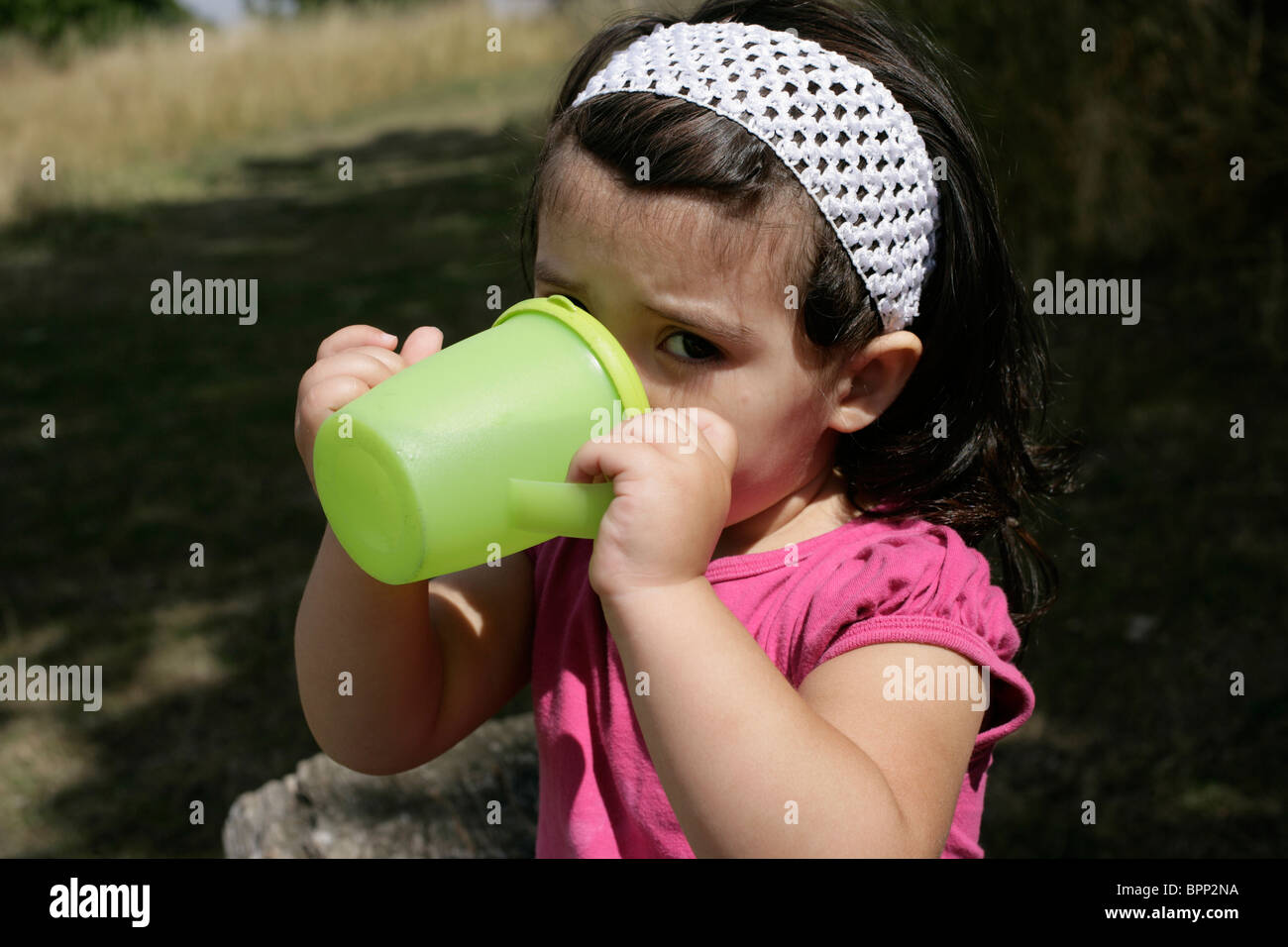 Two-year-old toddler drinking to quench her thirst in the park - Stock Image