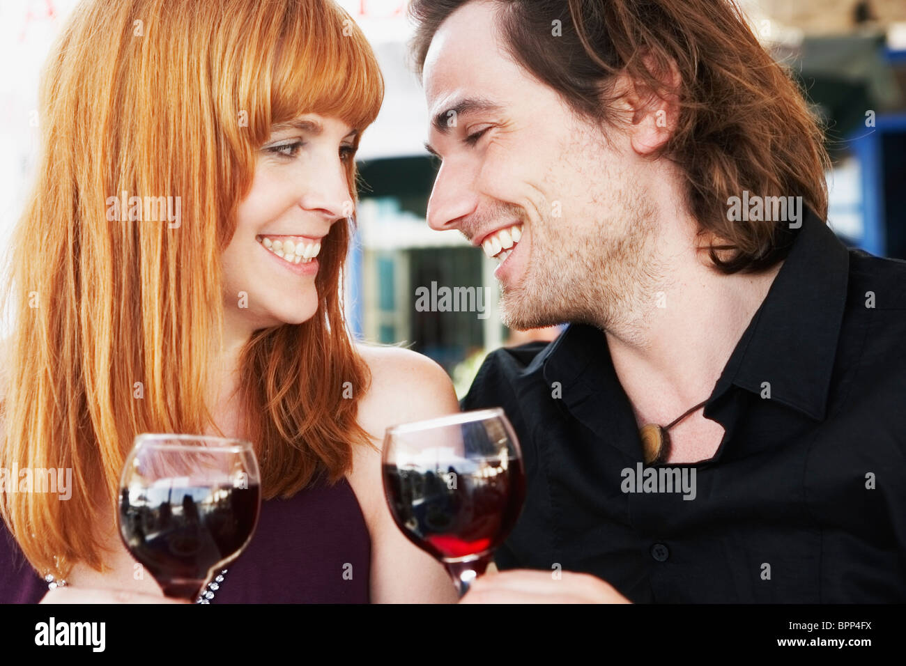 Young couple clinking glasses - Stock Image