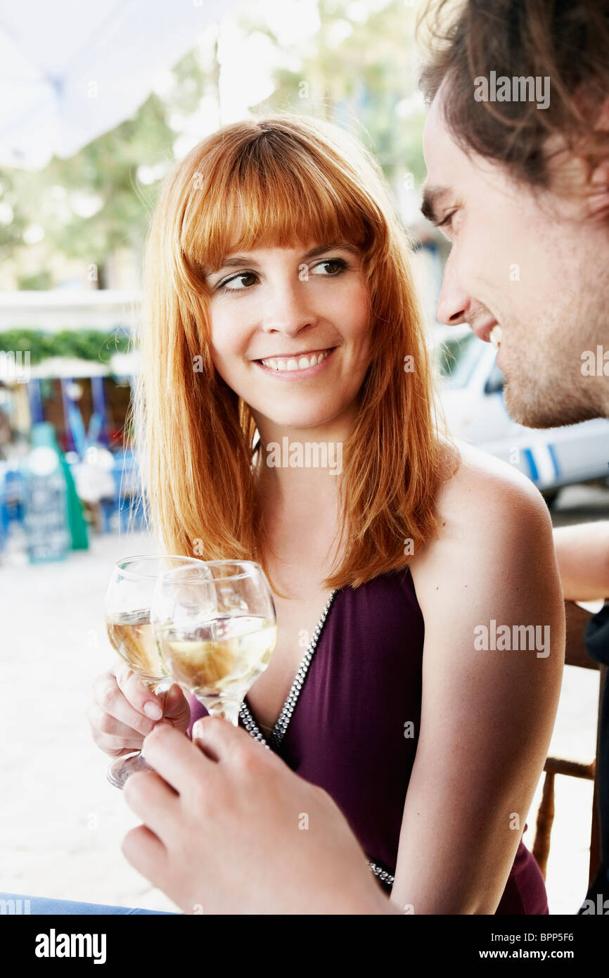 Couple clinking glasses with white wine - Stock Image