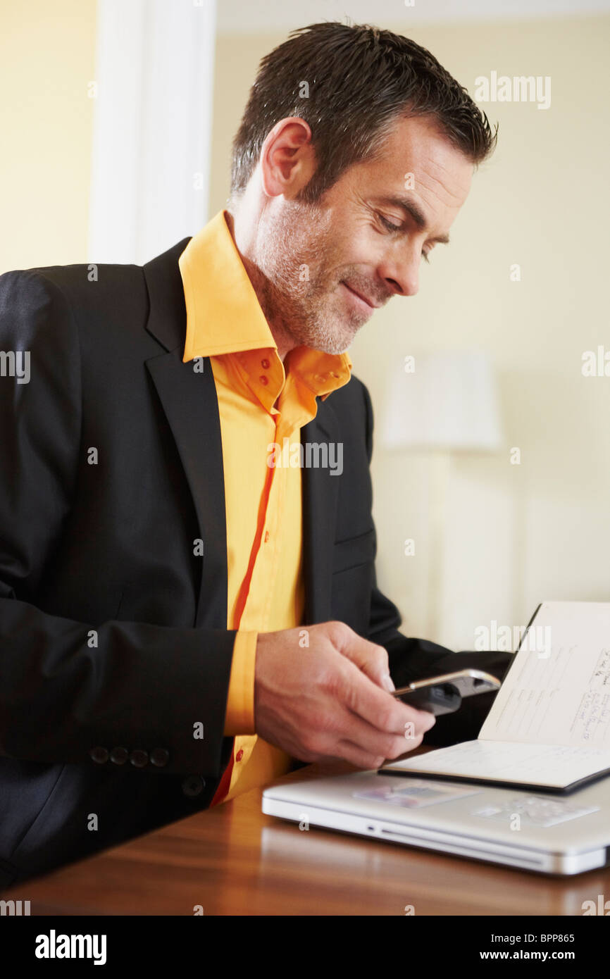 Man dialing number on cellphone - Stock Image