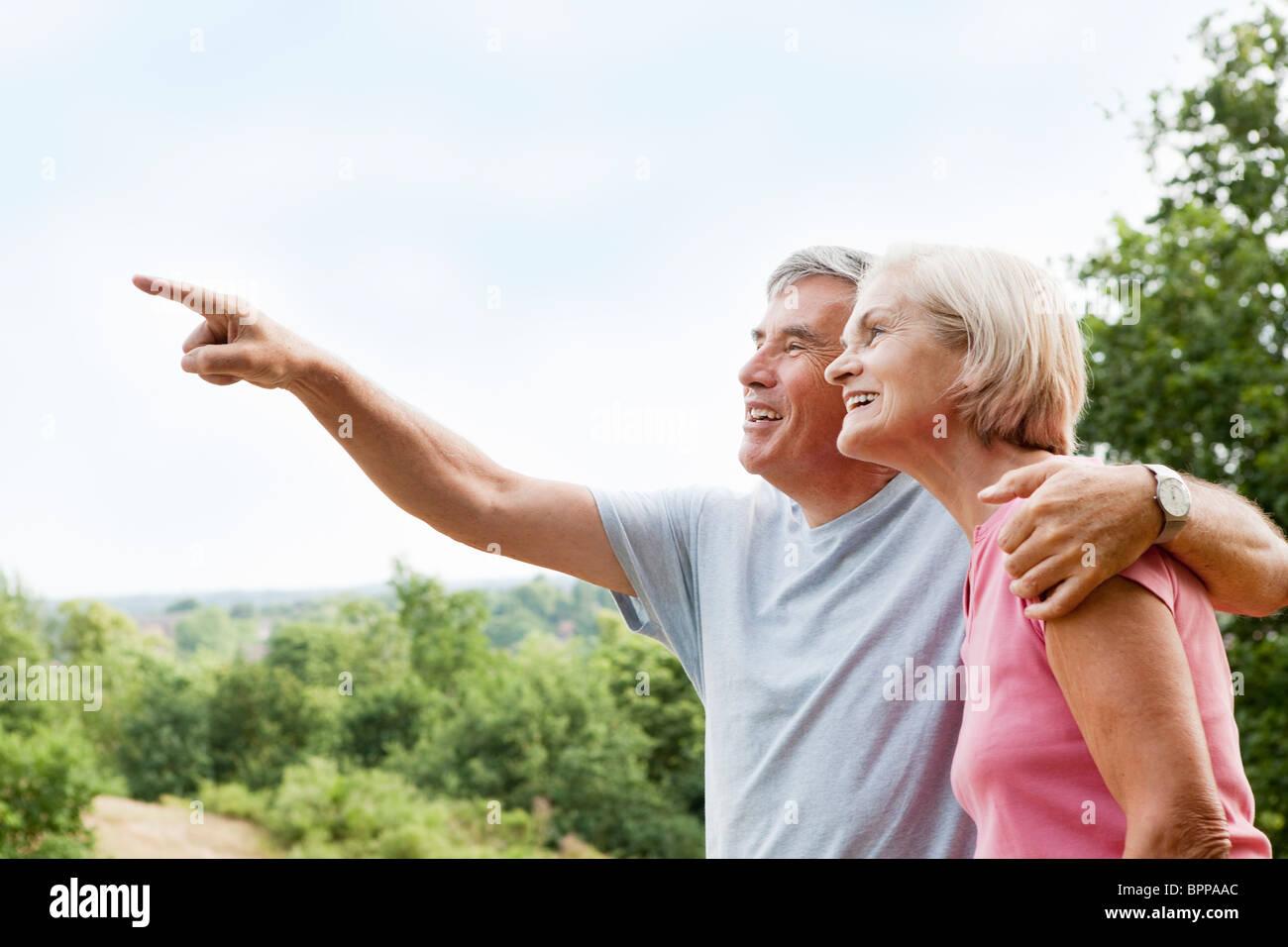 Mature man embracing woman points away - Stock Image