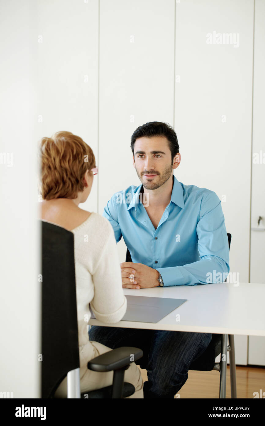 Man sitting opposite woman in office - Stock Image