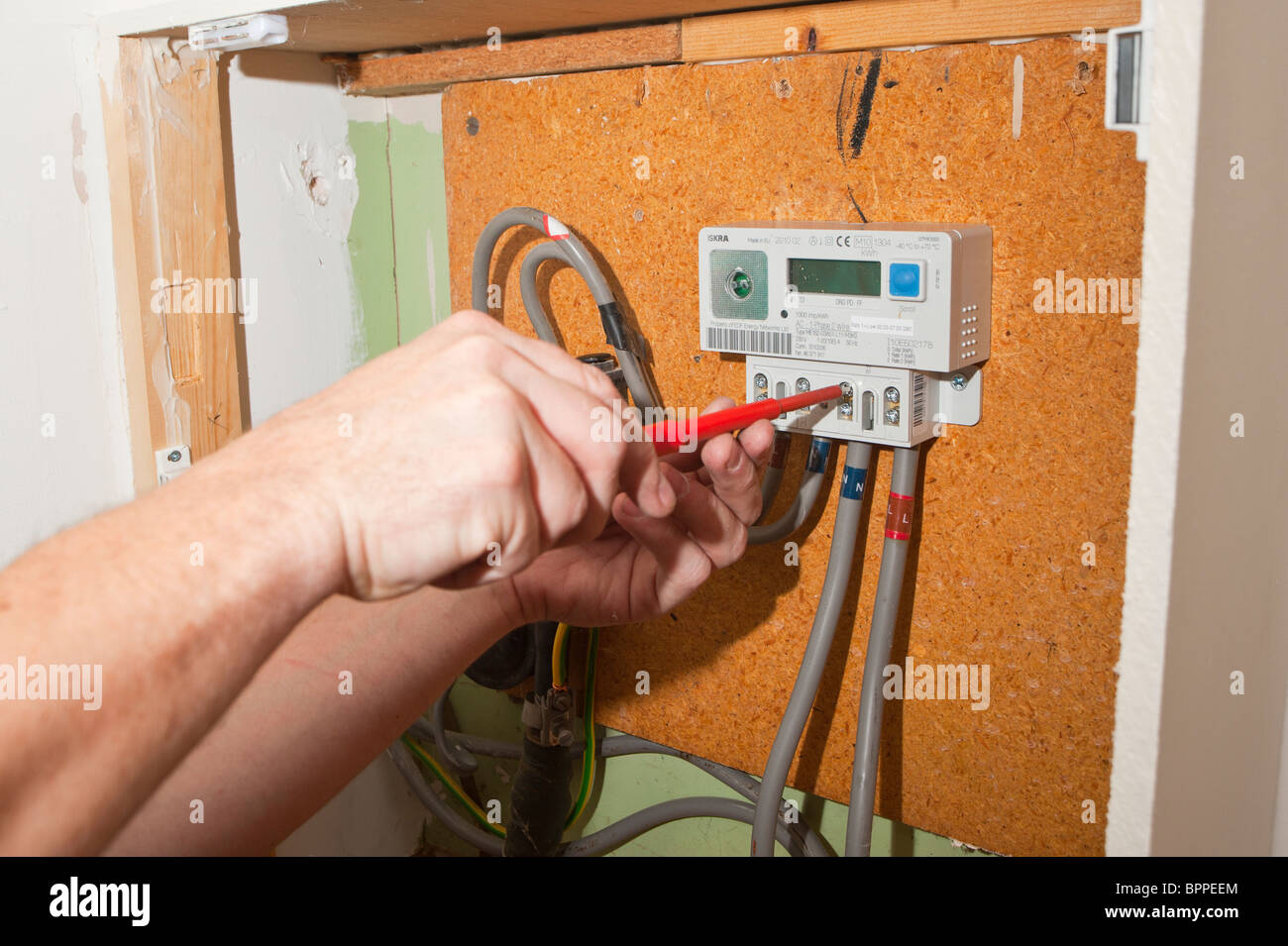 An electrician fitting a new digital electric meter in the Uk - Stock Image