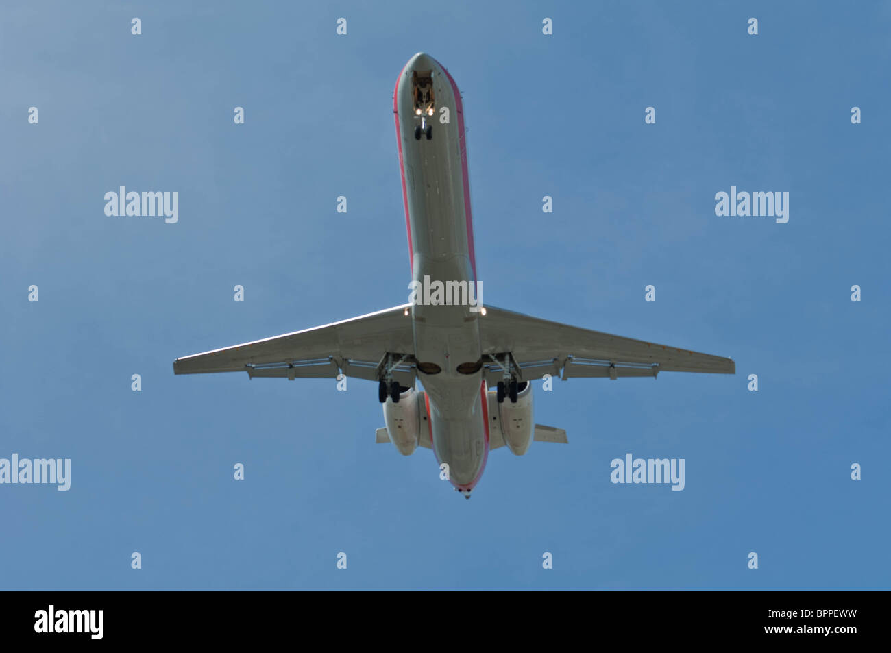 Underside of a passenger jet on a landing approach to a runway with landing gear in the down position. - Stock Image