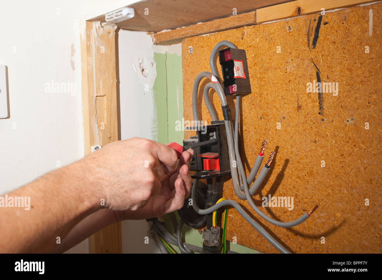 An electrician replacing an electric meter in the Uk - Stock Image