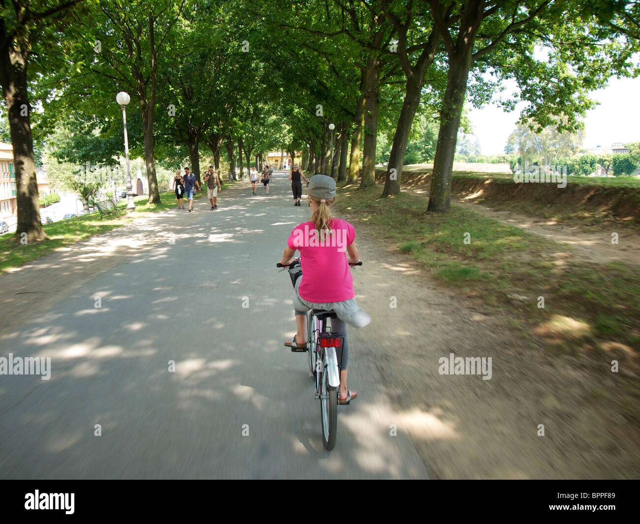 Girl 10 years old riding a rented bicycle on the historic city wall in Lucca, Tuscany, Italy - Stock Image