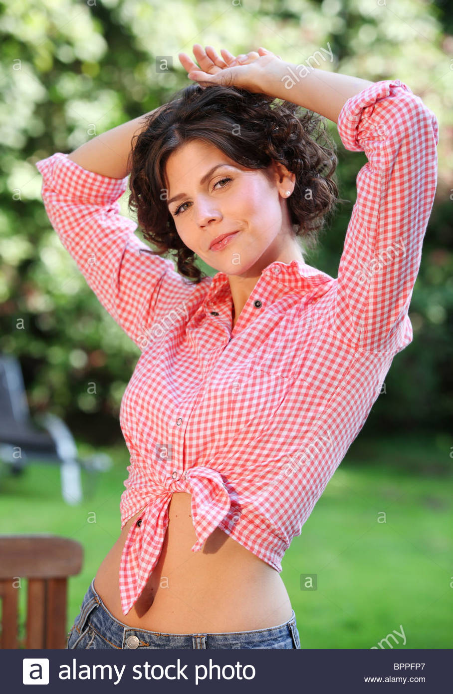 portrait of young brown-haired woman in garden - Stock Image