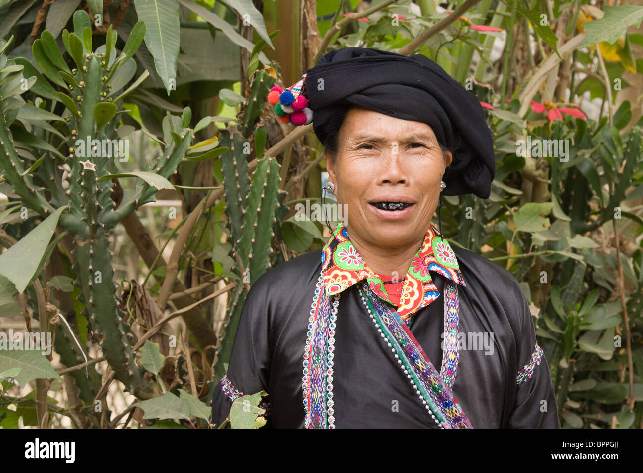 Photograph of a Lu minority wearing traditional clothing with her teeth blackened woman in front of a cactus Stock Photo