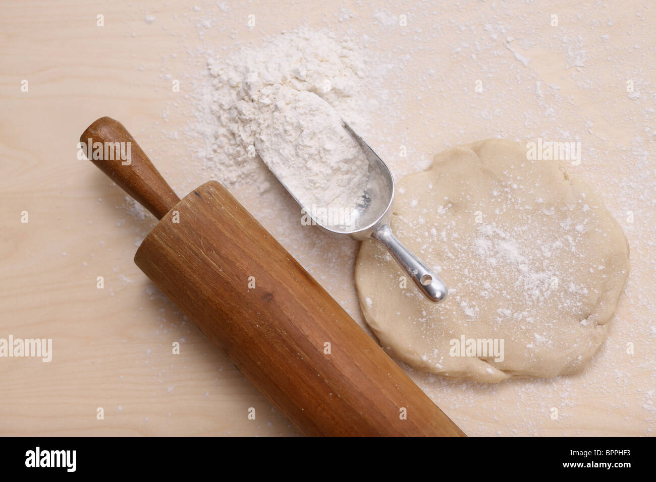 Baking, rolling pin, scoop of flour and dough - Stock Image