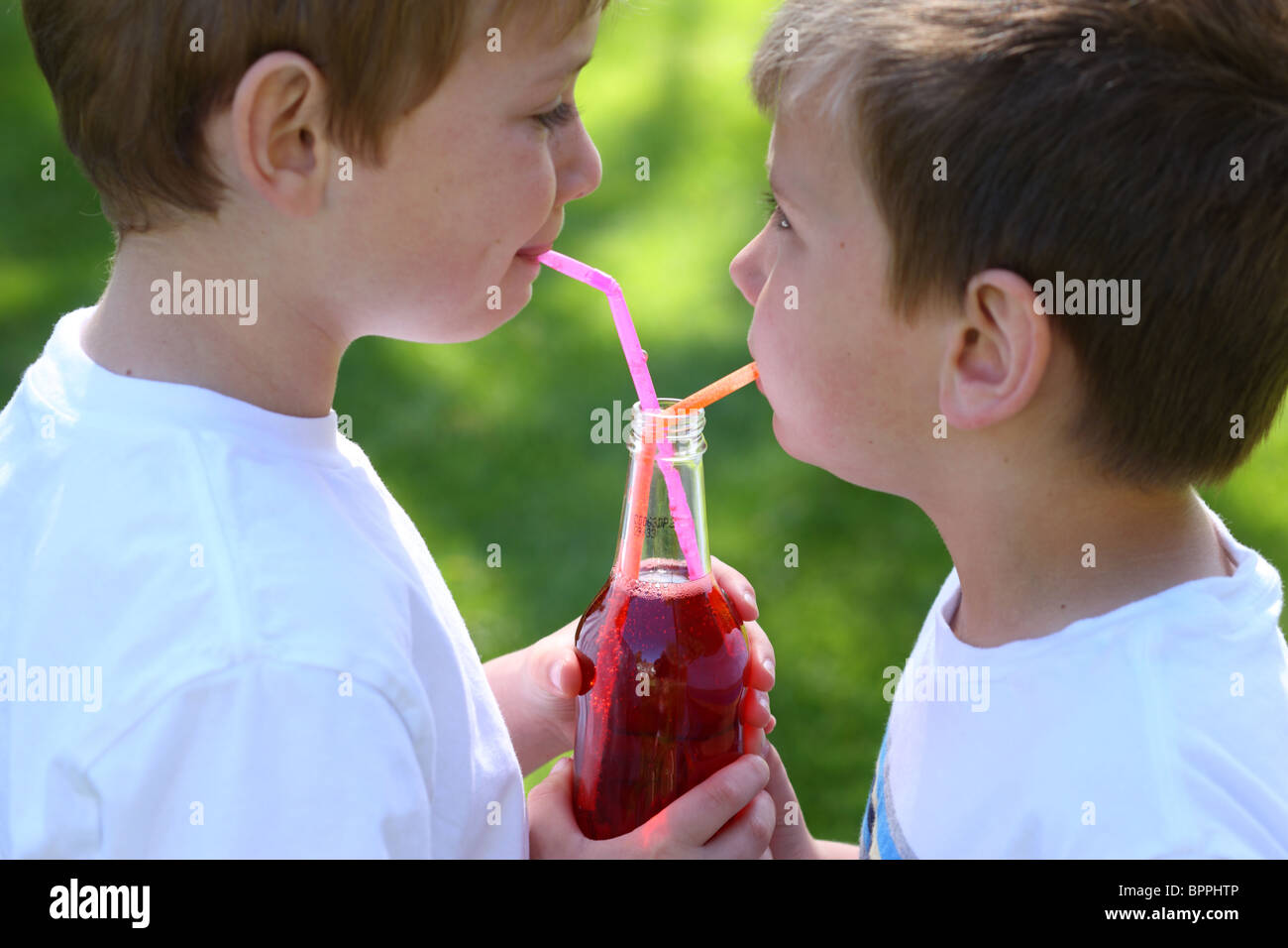 Two young boys sharing bottle of soda - Stock Image