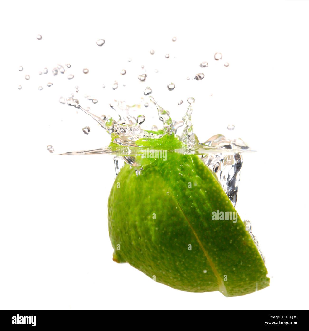 Lime splashing into water studio isolated on white background - Stock Image