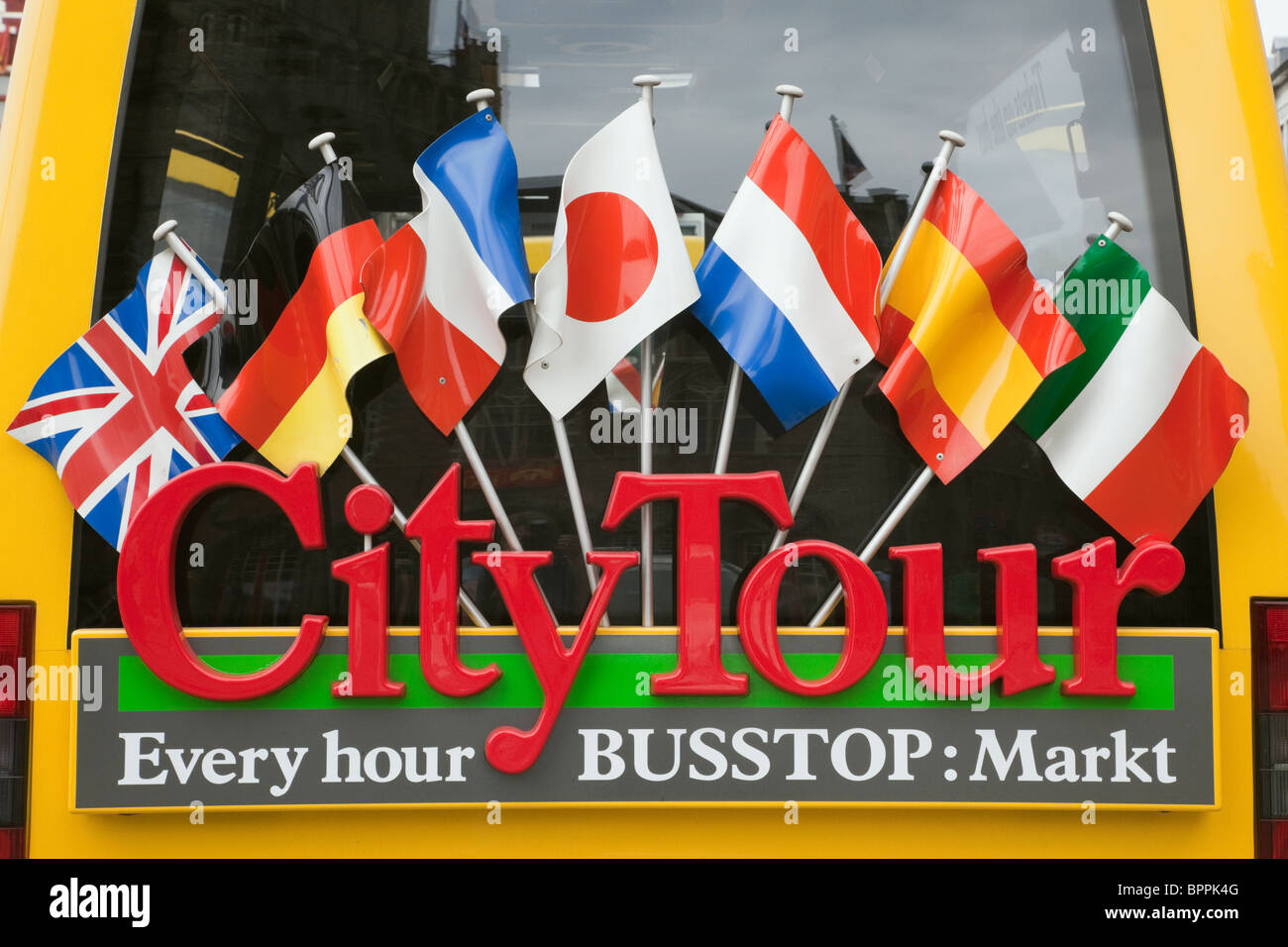 Rear of a City Tour bus decorated with international flags. Markt, Bruges, Belgium, Europe. - Stock Image