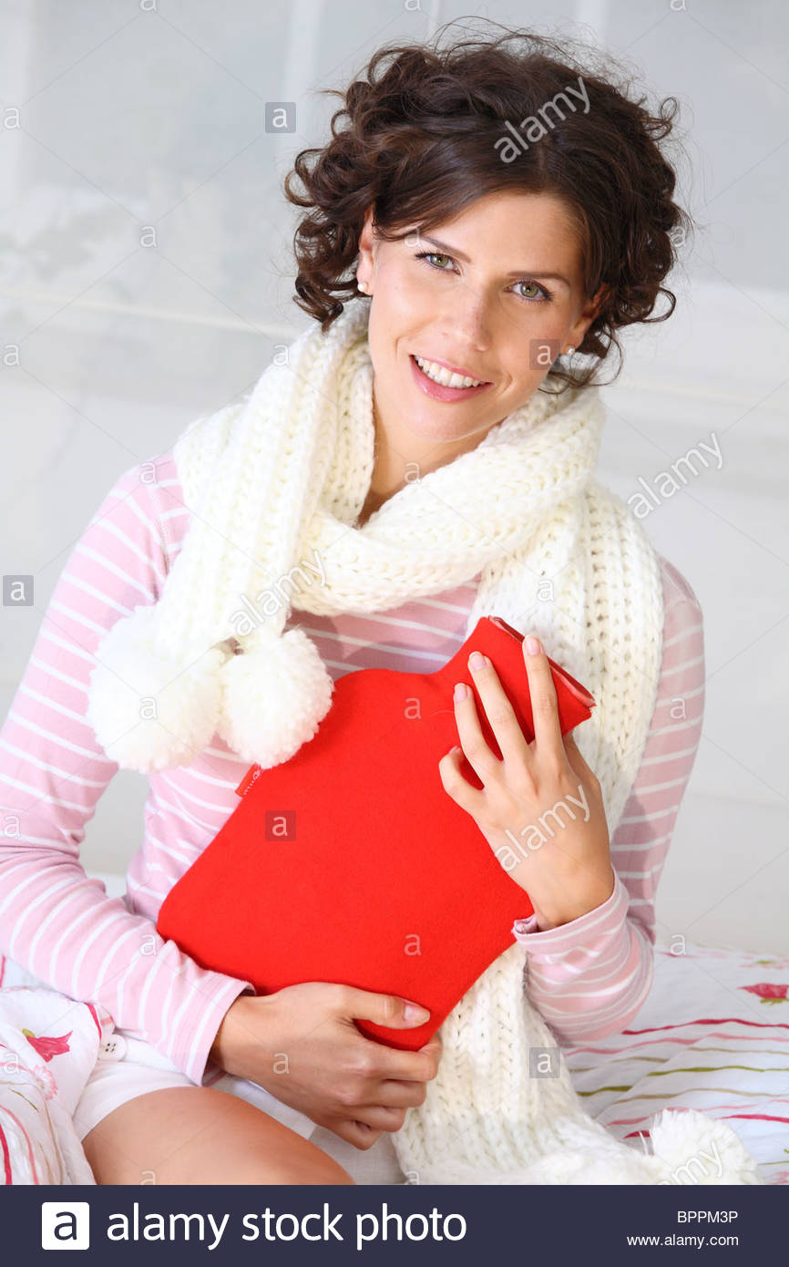 woman in bed holding hot water bottle - Stock Image