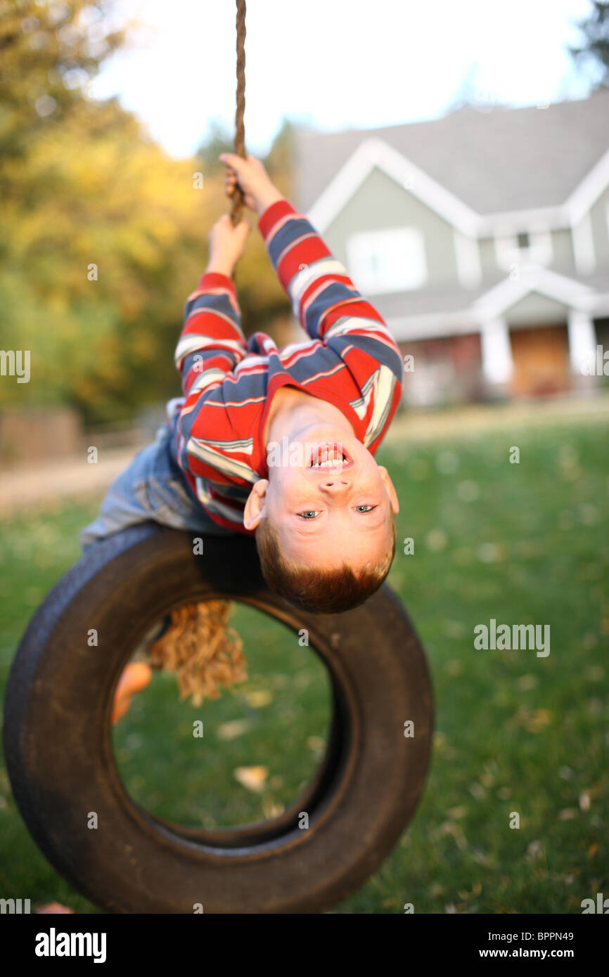 Young boy on tire swing - Stock Image