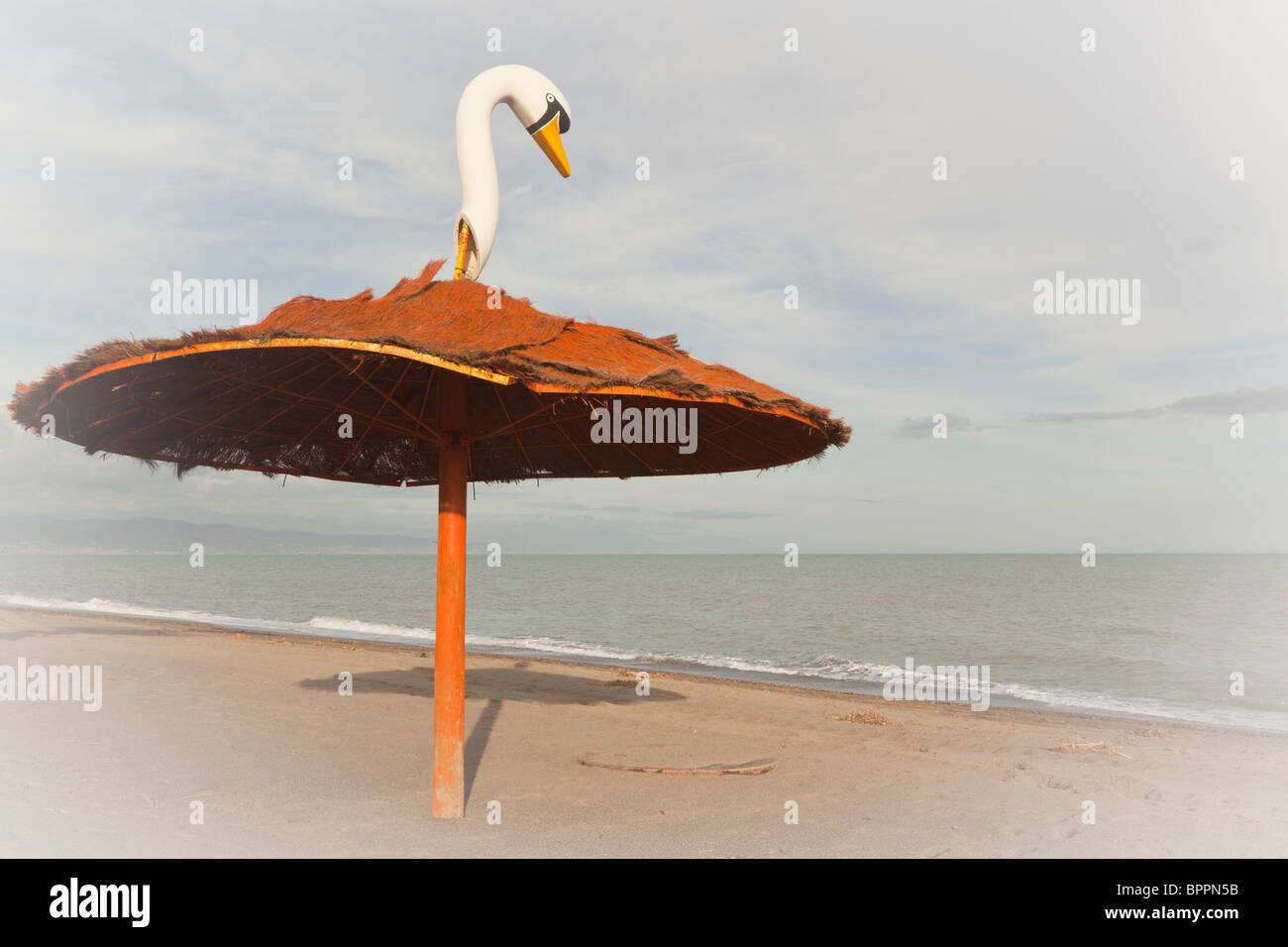 Sunshade with swan's head attached to top on Playamar beach, Torremolinos, Malaga Province, Costa del Sol, Spain - Stock Image