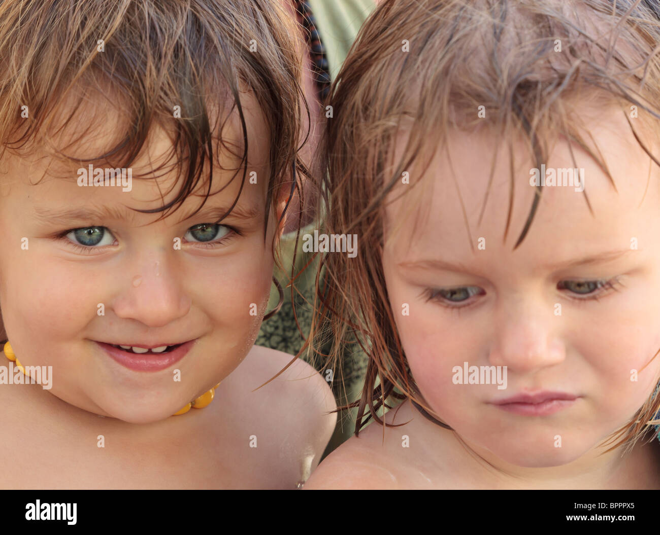 Two two year old girls, one happy, one sad. - Stock Image