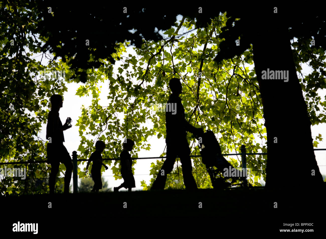 The outline of a family strolling in the Napoleon III Park in Vichy (France). Woman and man with children. - Stock Image
