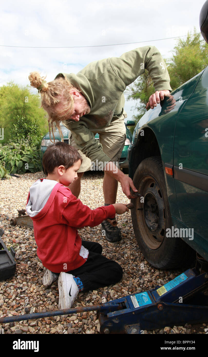 Young mother and son changing a tyre on a car. - Stock Image