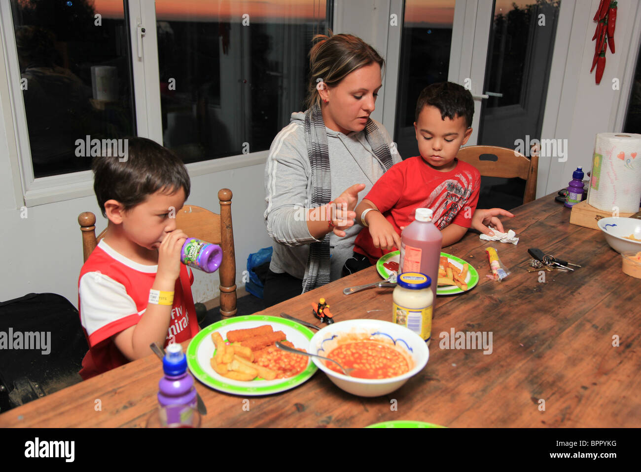 Young boys having their dinner with mum. - Stock Image