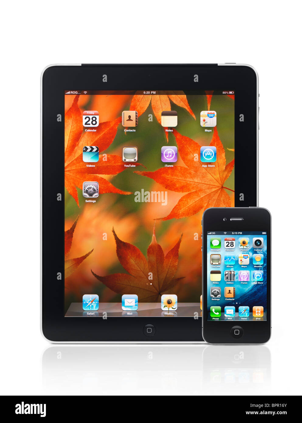 Apple iPad 3G tablet computer and iPhone 4 smartphone with desktop icons on their displays isolated on white background. - Stock Image