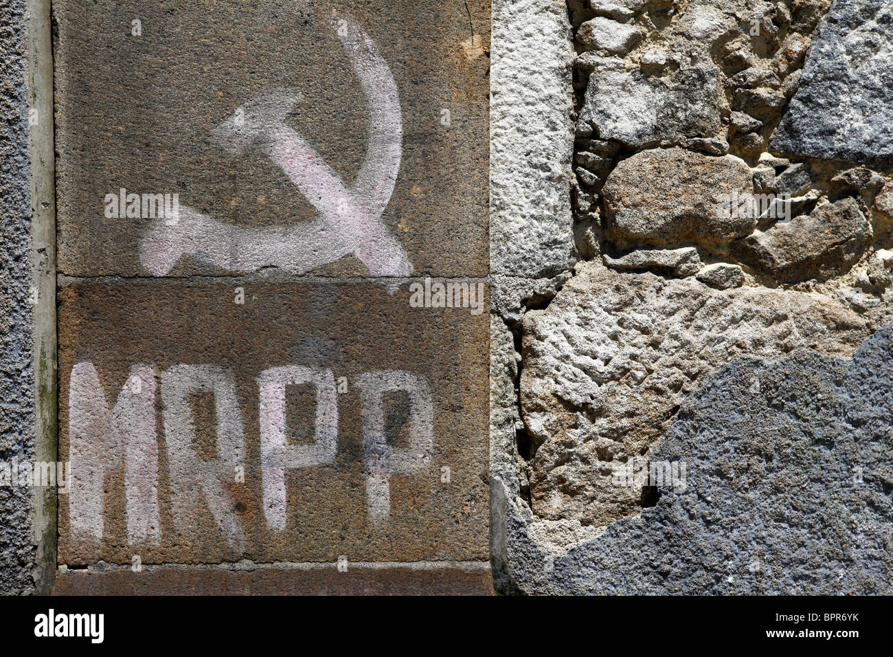 A Communist hammer and sickle symbol in daubed onto a wall in Braga, Portugal. - Stock Image