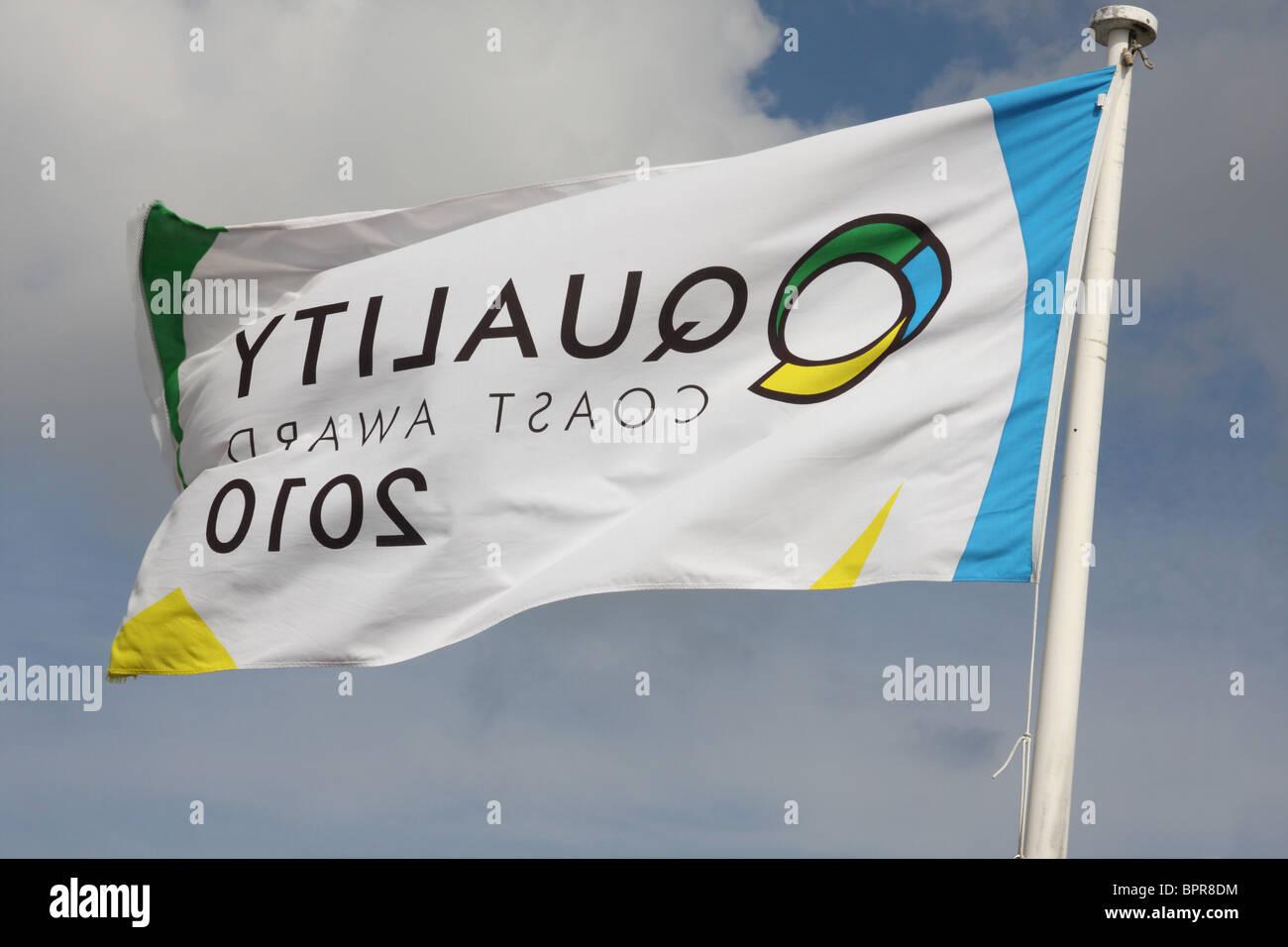 A Quality Coast  Award 2010 flag on a U.K. beach. - Stock Image