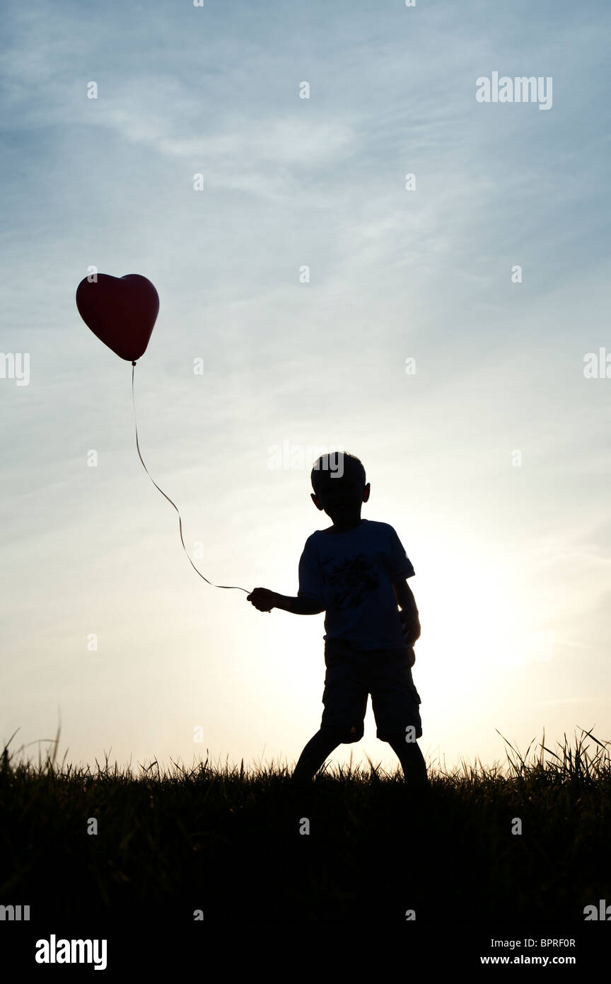 Silhouette of a young boy playing with a heart shape balloon at sunset - Stock Image