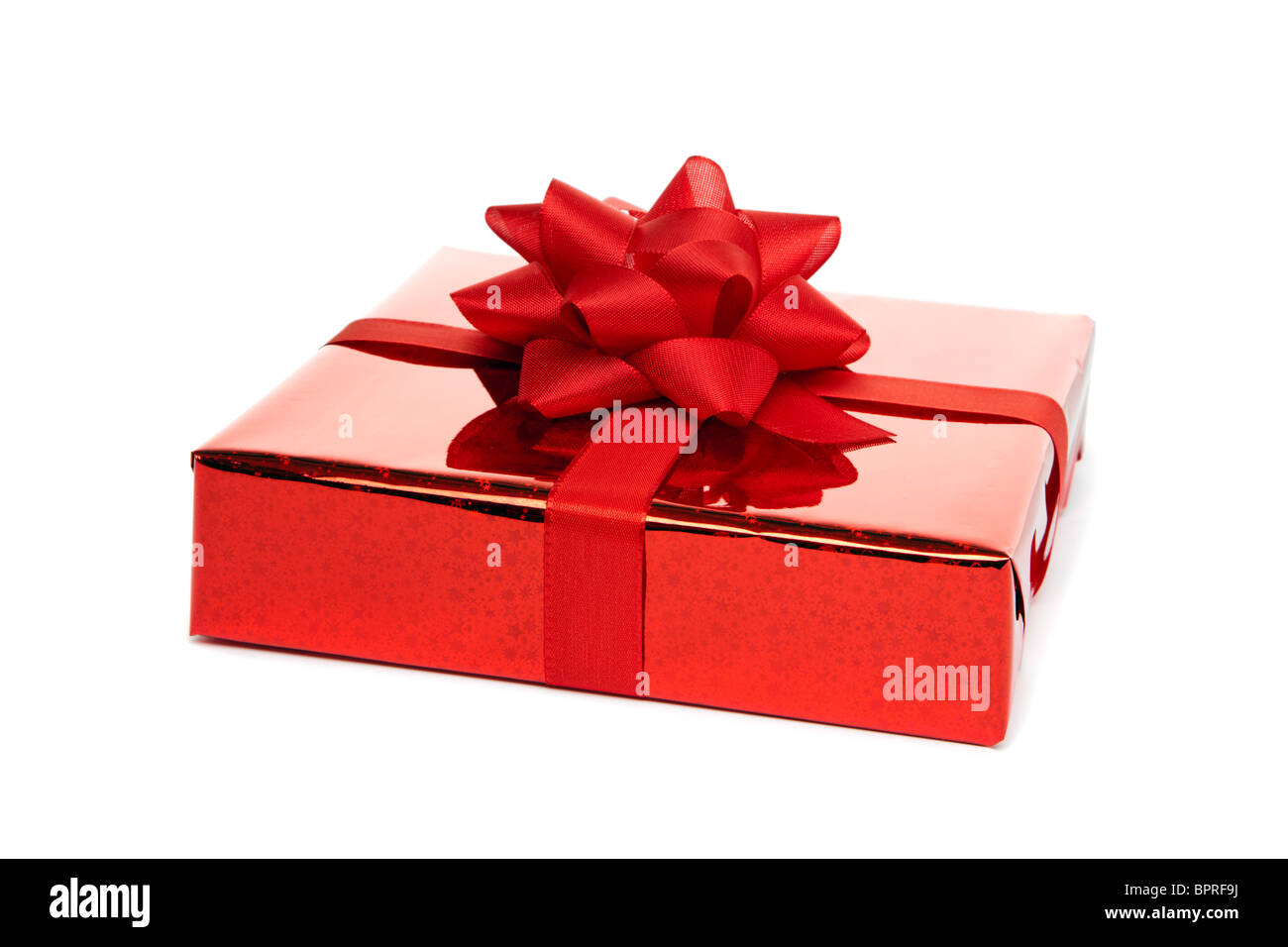 birthday or christmas gift wrapped in red foil and ribbon with large bow, isolated on  white background Stock Photo