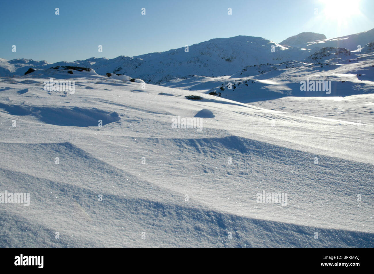 Snow drifts on the summit of Seathwaite Fell in the Lake District - Stock Image