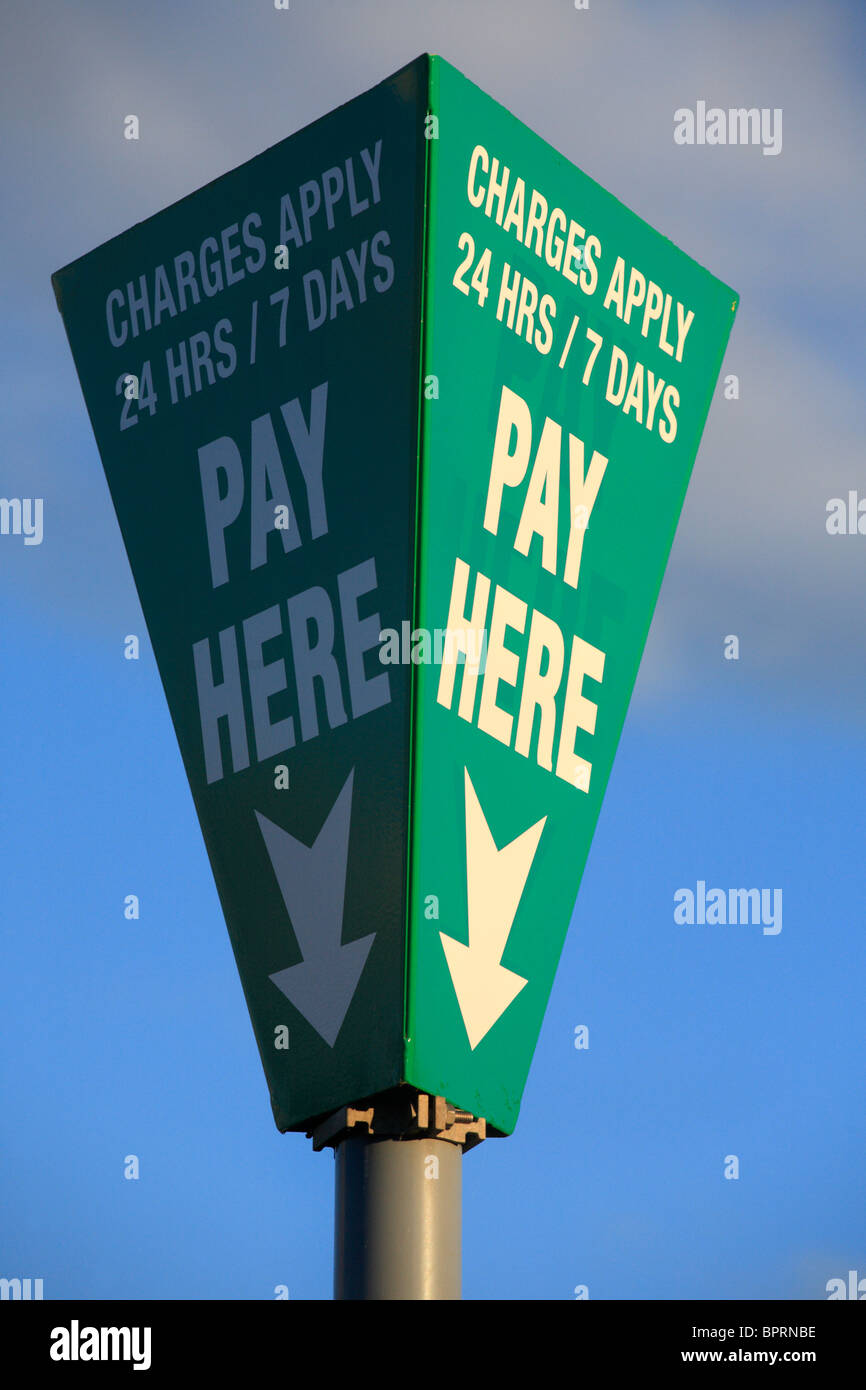 Sign post in a car park indicating where to pay and that charges apply 24/7. - Stock Image