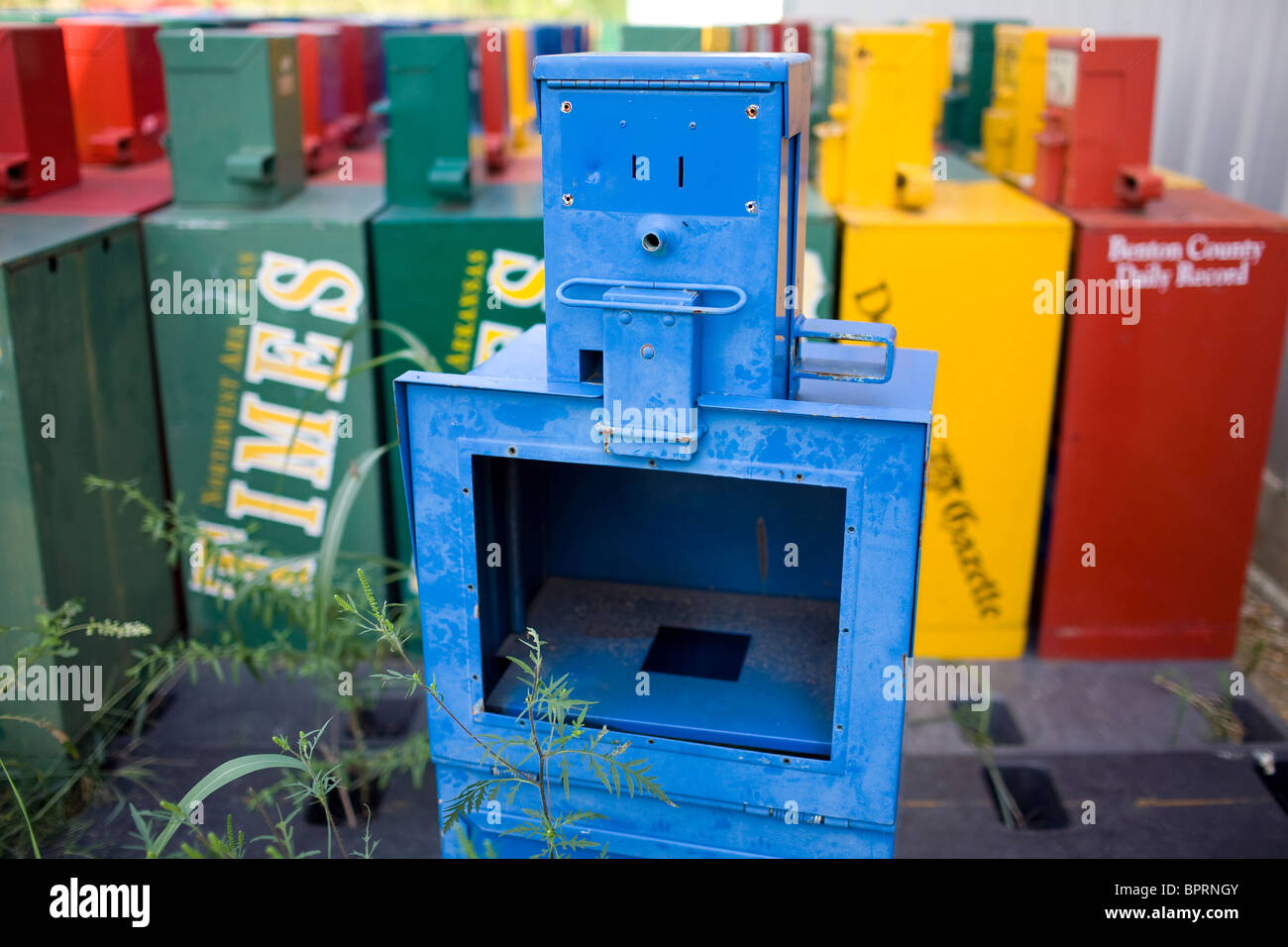A surplus newspaper box possessing a human-like expression sits behind a building in Springdale, Ark. - Stock Image