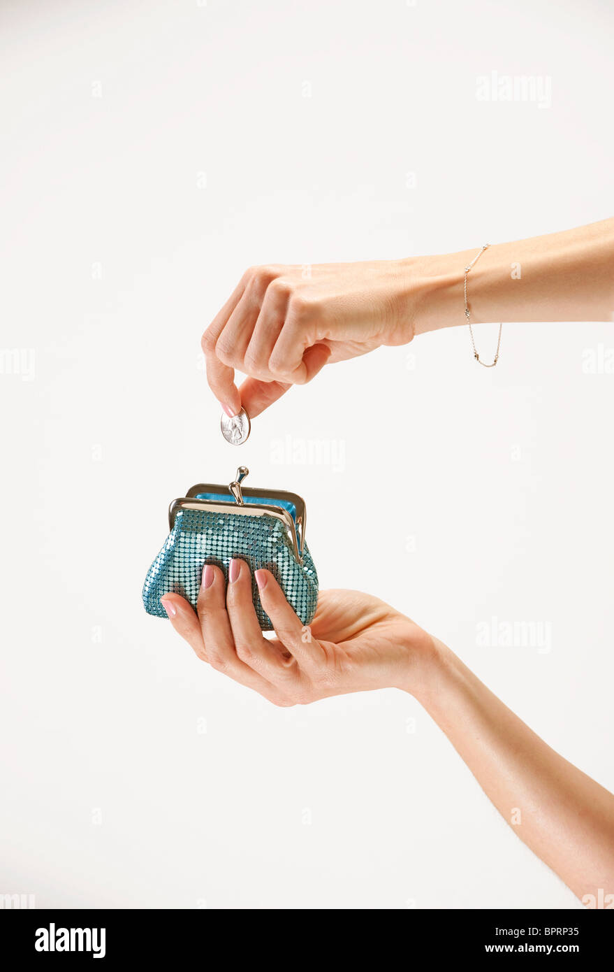 woman takes quarter from her blue coin purse - Stock Image