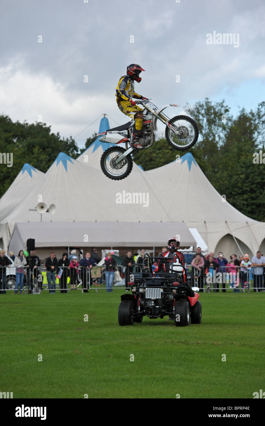 Motorcycle stuntman flies into the air over the head of another stunt man as crowds watch him at a summer show Stock Photo