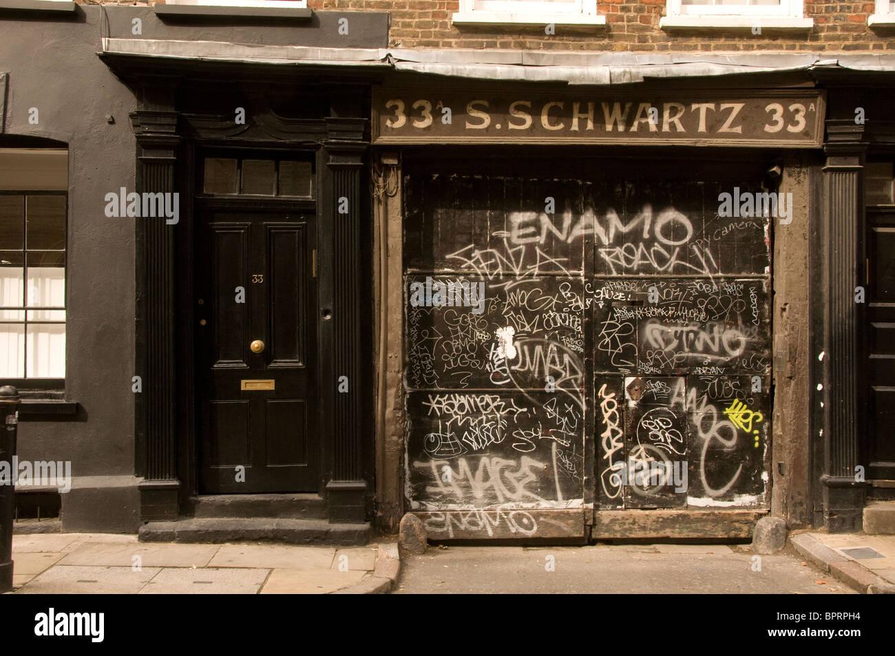 graffitti on vandalized building near Brick Lane London UK - Stock Image