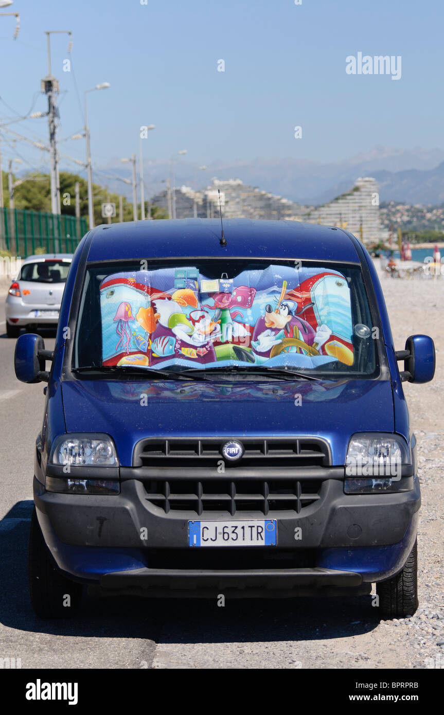 Italian Fiat car parked beside a beach with a Disney sunscreen in the windscreen to prevent heat build-up. - Stock Image