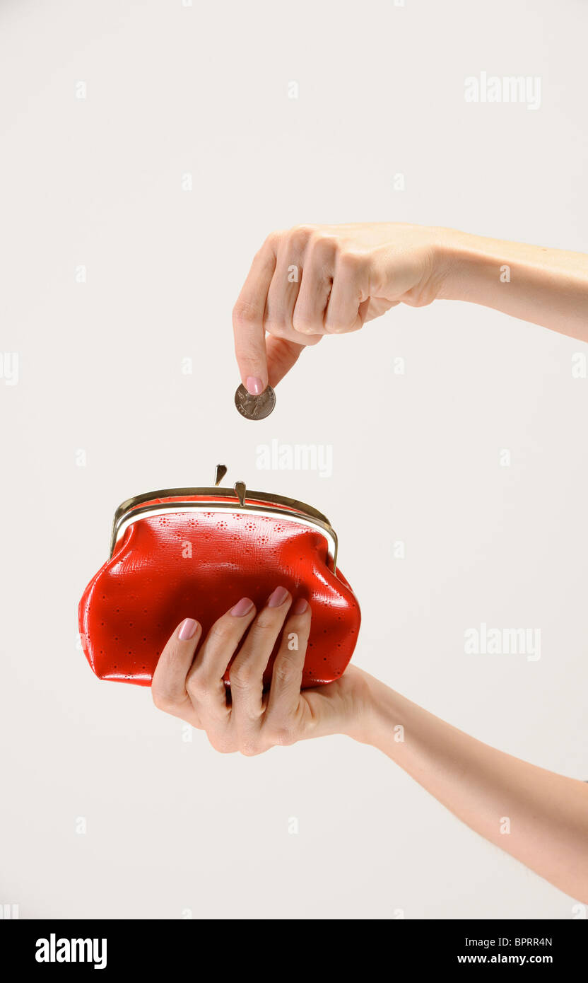 woman's hands put coin into big red purse - Stock Image