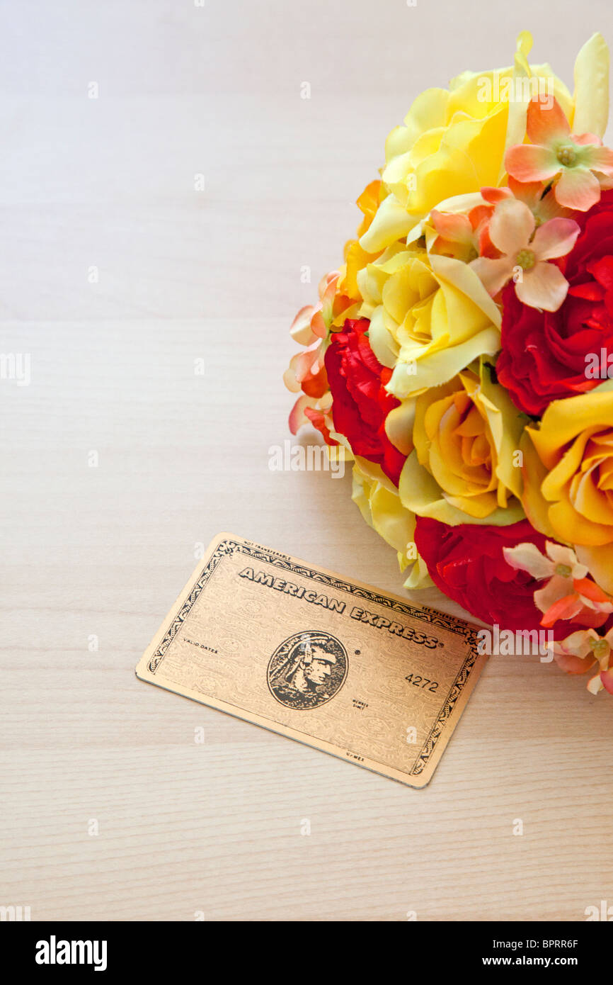 American Express gold card next to flowers - Stock Image