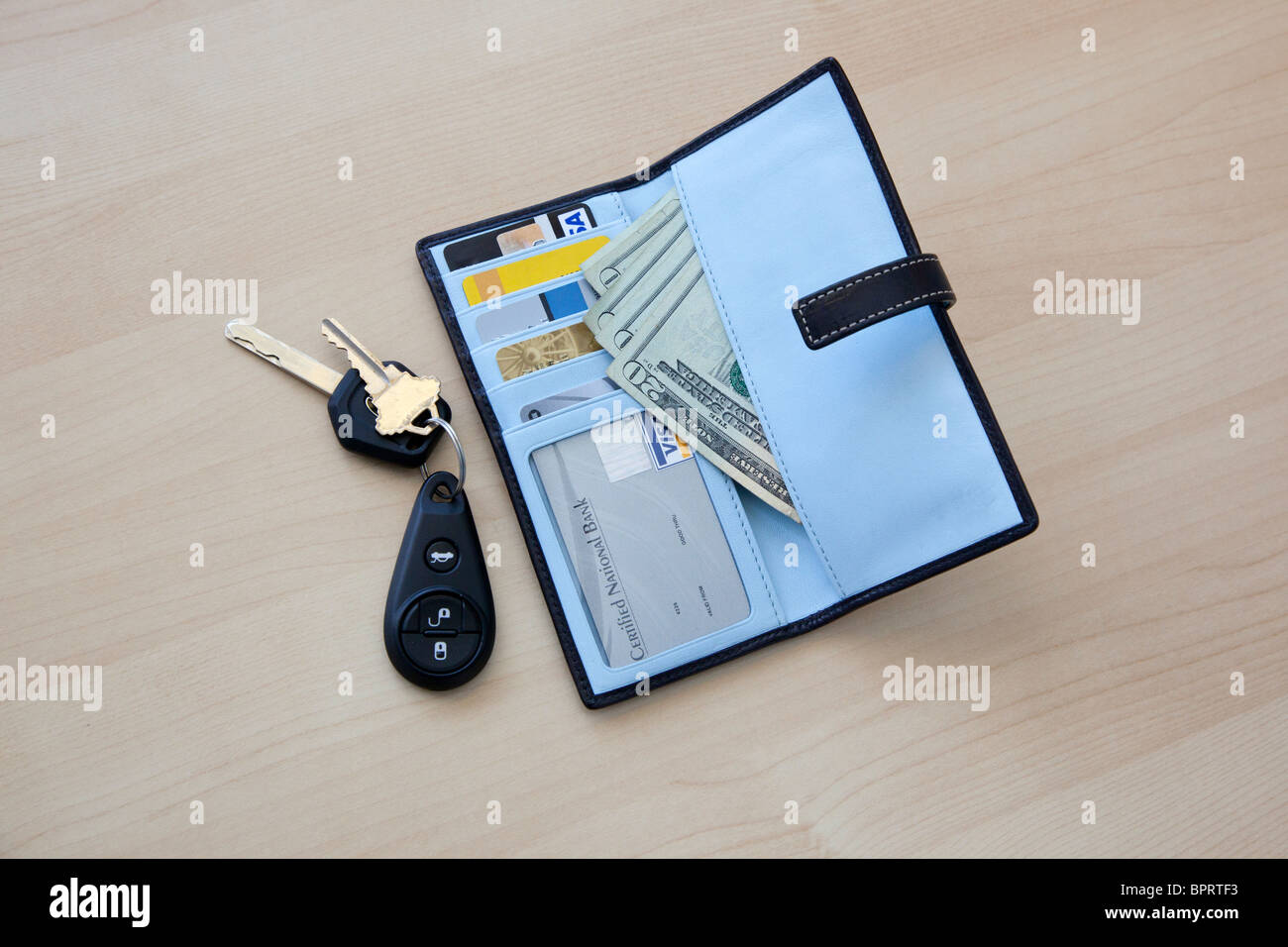 wallet with money and cards and car keys on table - Stock Image