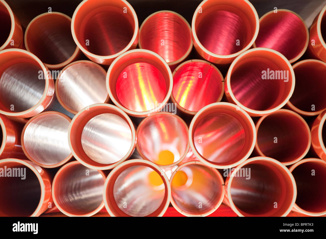 Brown PVC pipes stacked in construction site - Stock Image