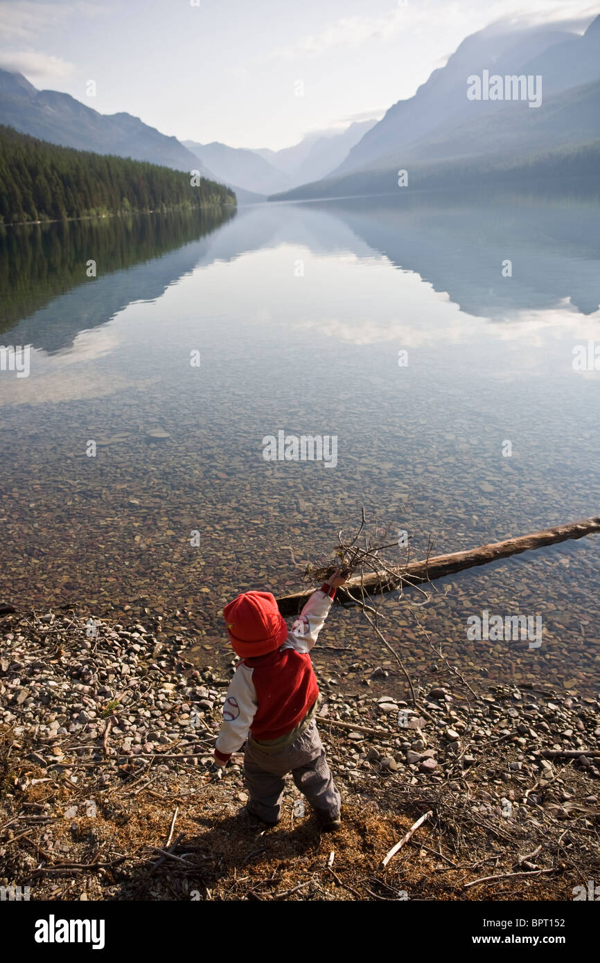 Young boy throwing a handful of wooden twigs into Bowman Lake at Glacier National Park, Montana. - Stock Image