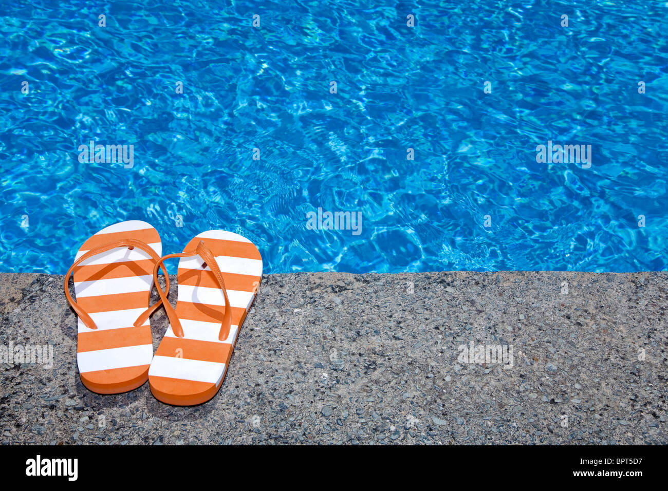 Pretty pair of stripey flip flops or thongs next to a sparkling blue swimming pool Stock Photo