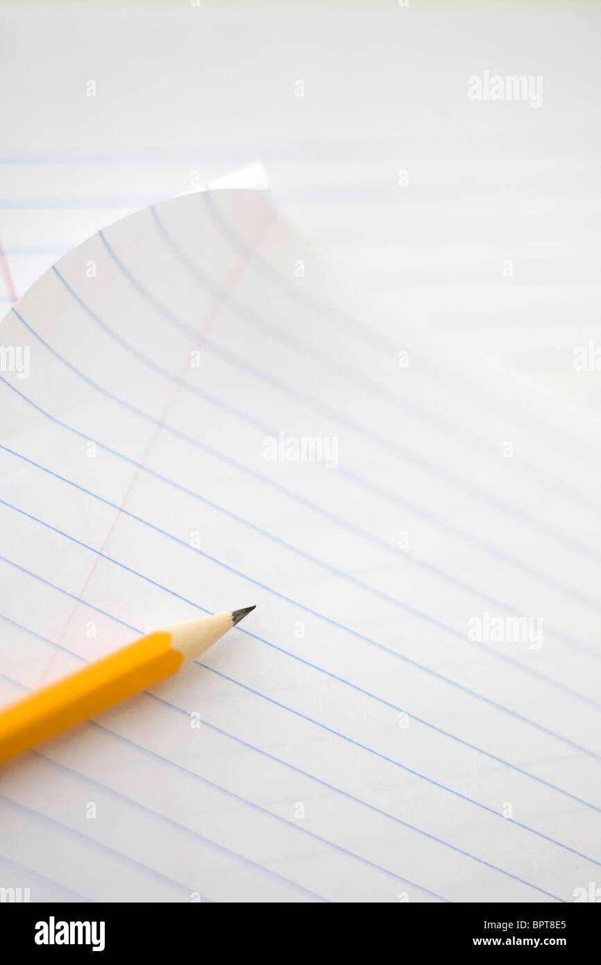 yellow school pencil on lined note book paper - Stock Image