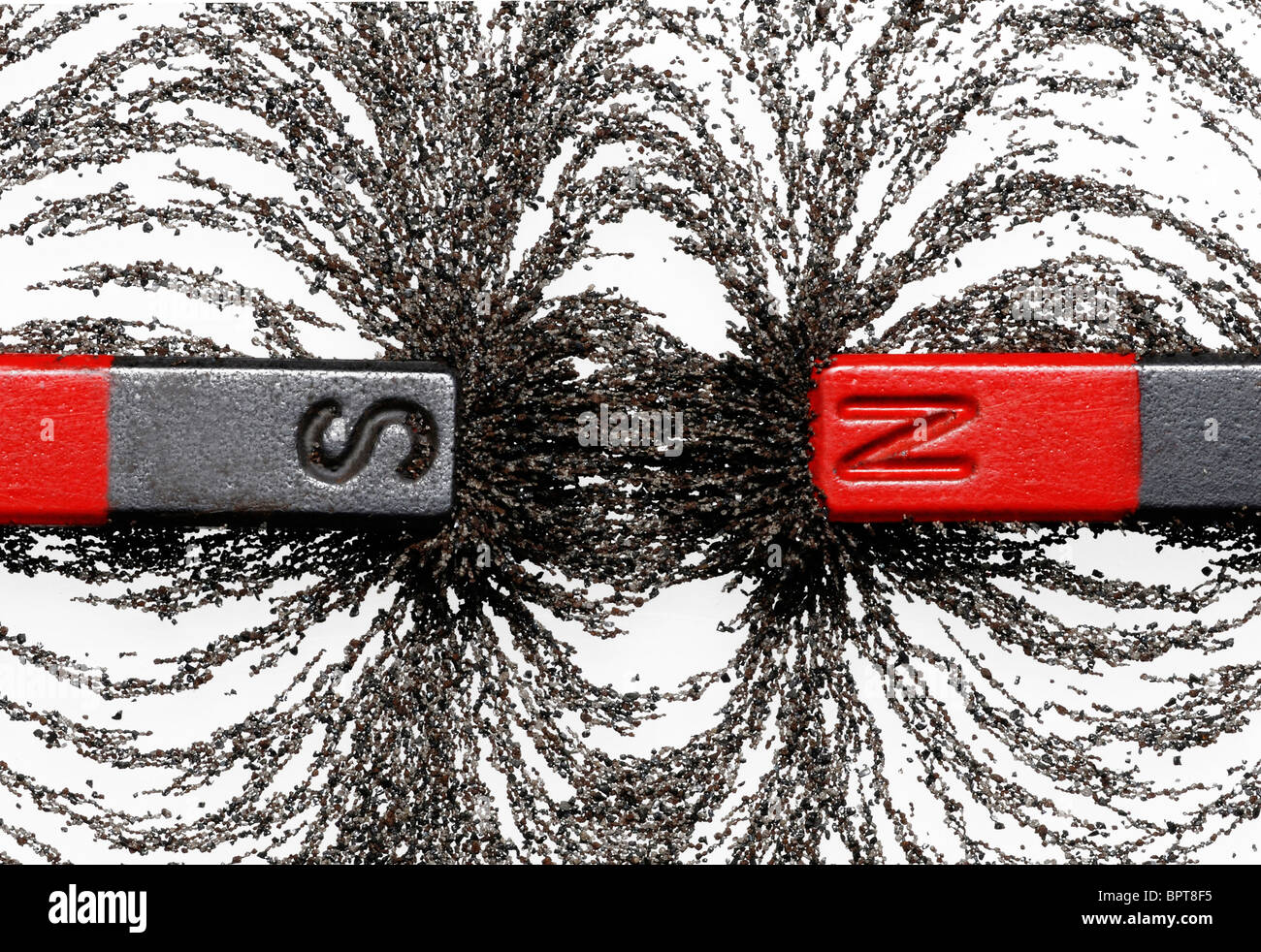 Bar magnets with iron filings showing magnetic attraction between opposite poles - Stock Image