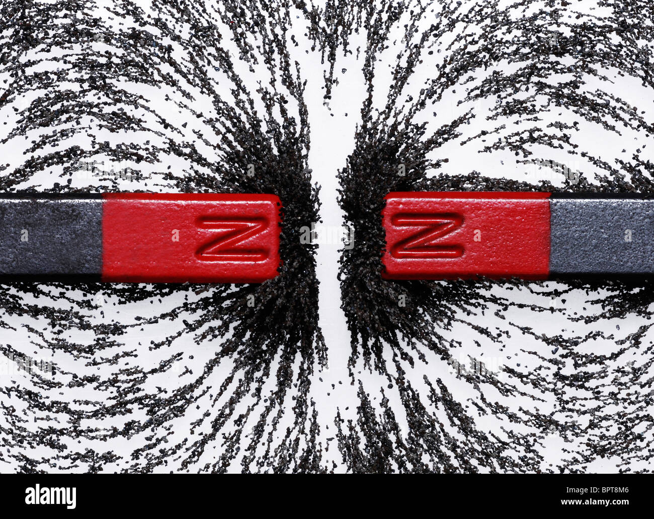 Bar magnets with iron filings showing magnetic repulsion between similar poles - Stock Image