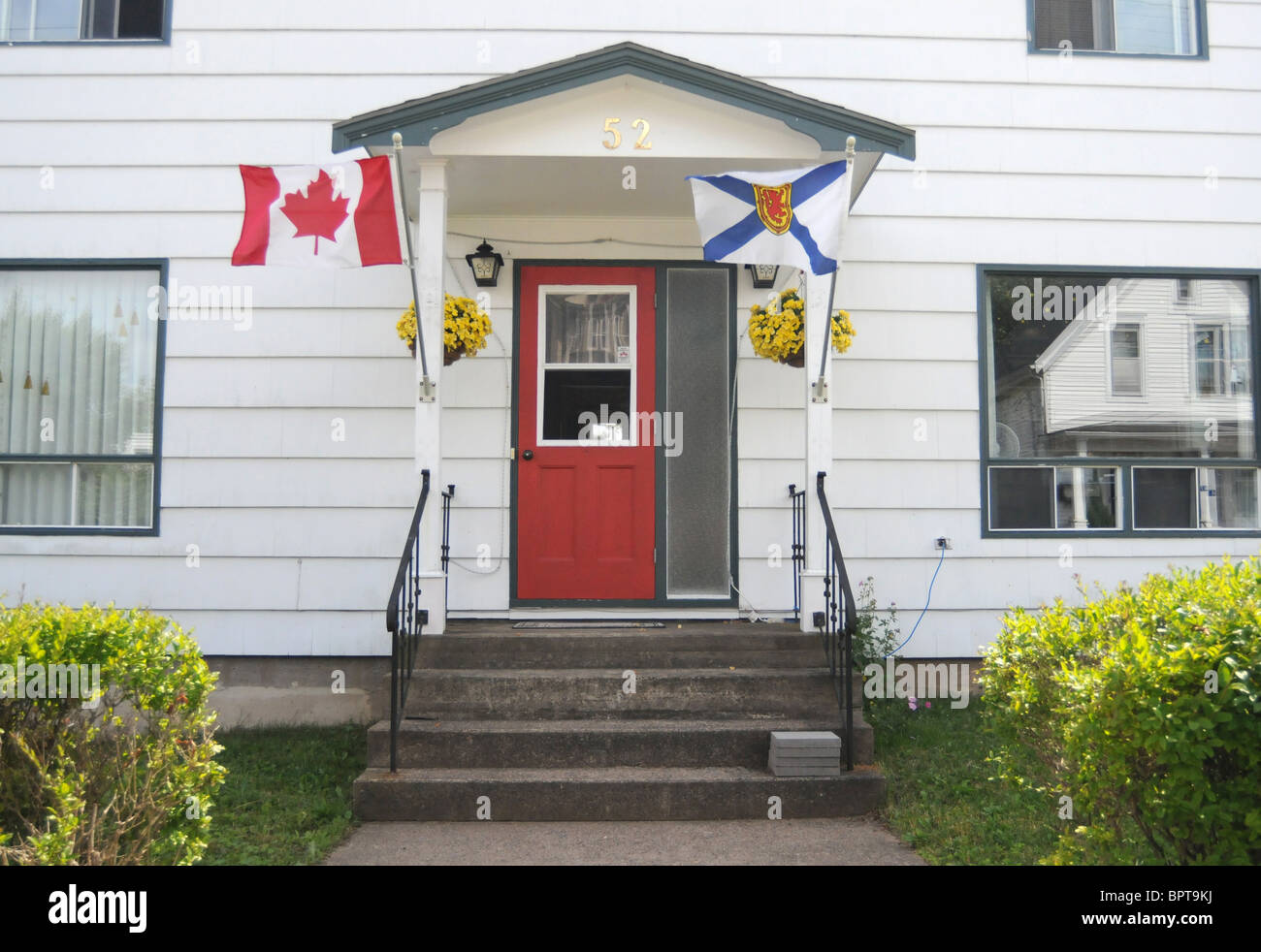The flags of Nova Scotia and Canada are seen flying outside the home of a patriotic Canadian in Lunenburg, Nova Scotia, Canada. Stock Photo