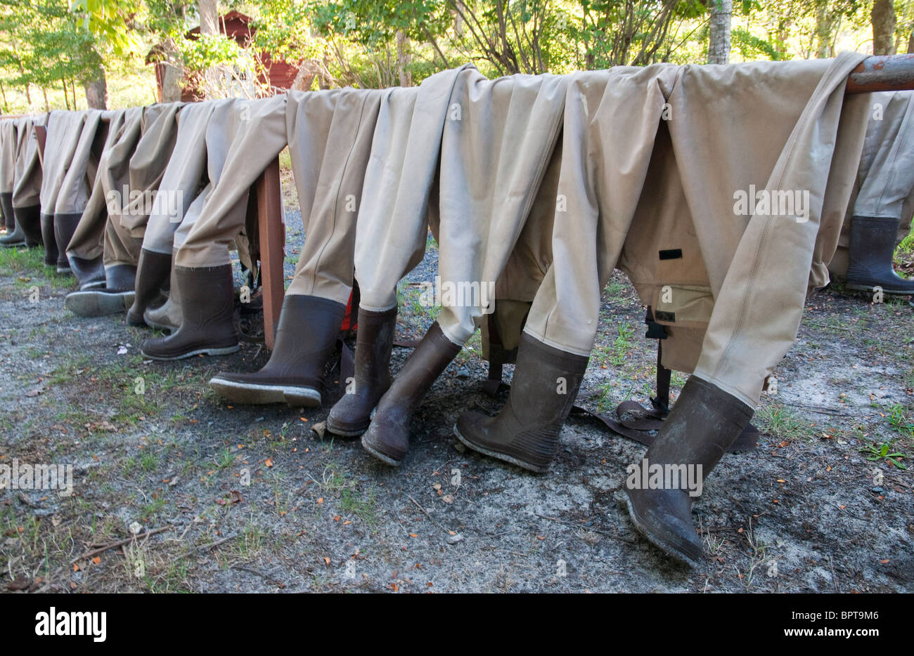 Fishing gaiters lined up on a railing Stock Photo