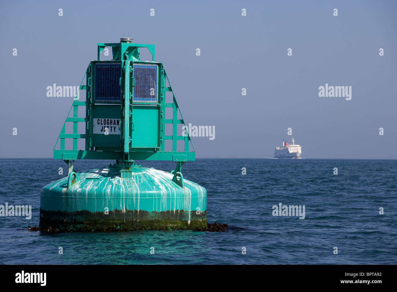 Belfast lough cloghan point maritime navigation buoy warning marker with ferry in the background - Stock Image