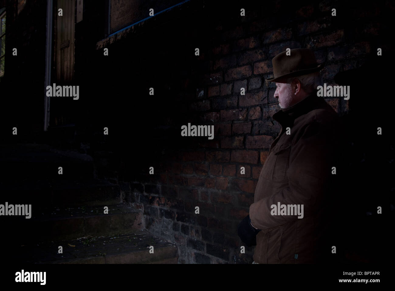 Film Noir depicting a quiet and dangerous man waiting in a darkened alley. - Stock Image