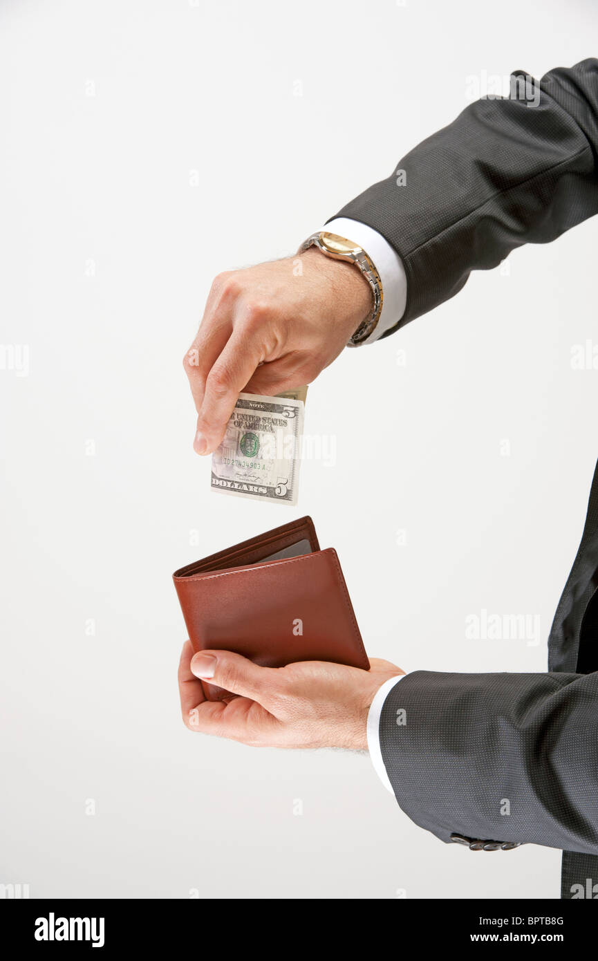 Man puts money into his wallet - Stock Image